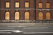 London's empty Goodge Street with traffic direction arrows are seen outside the derelict Middlesex Hospital building whose windows are boarded up with plywood.