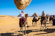 A teenage girl appears to hold up a rock. A family rides camels at the Giza Pyramid Complex, Giza, Egypt.