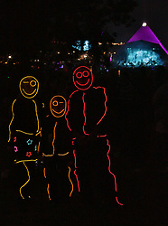 A family dressed in dayglo suits pose for photos in front of the Pyramid stage during Radiohead's headline performance on Day 1 of the 2017 Glastonbury Festival at Worthy Farm in Somerset. Photo date: Friday, June 23, 2017. Photo credit should read: Richard Gray/EMPICS Entertainment