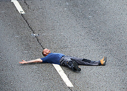 © Licensed to London News Pictures. 19/09/2017. HANSLOPE, UK. A man lies on the tarmac of an empty section of motorway on the closed carriageway of the M1 near Hanslope between junctions 15 and 14. The road has been closed since 7:30am this morning, trapping hundreds of people, as the police deal with a suspicious item found under a bridge. The location is very near to Hanslope Park, home to Her Majesty's Government Communication Office (HMGCC0, part of FCO.  Photo credit: Cliff Hide/LNP