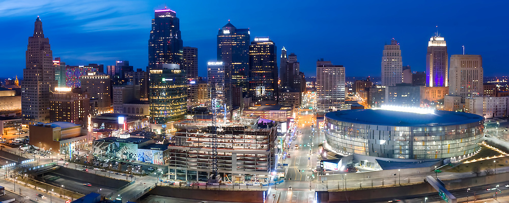 Panorama photo of Kansas City, Missouri's downtown skyline at dusk with Two Light Tower residential construction in foreground.