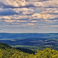 """""""On a Highland Wind""""<br /> <br /> Wondrous beauty of the scenic Laurel Highlands of PA.! Gorgeous vistas from atop a mountain looking out into layers of puffy clouds, down into the valley below, and across to other mountains. Beautiful shadows and light dance across the landscape from the clouds and sunlight above as a falcon soars by on the wind!!<br /> <br /> Laurel Highlands Area of Pennsylvania by Rachel Cohen"""