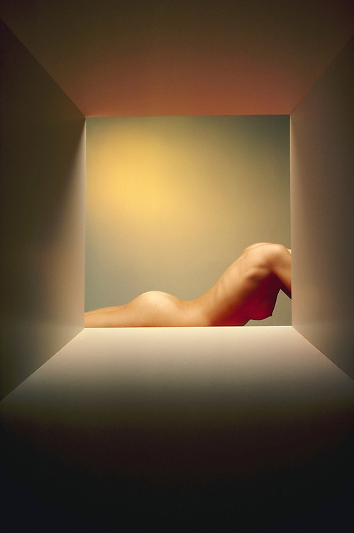Nude woman's torso in box with red light illuminating her breast and yellow light on wall behind her