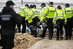 Steeple Claydon, UK. 23 February, 2021. Thames Valley Police officers arrest an activist during an operation by National Eviction Team bailiffs acting for HS2 Ltd to evict activists opposed to the HS2 high-speed rail link from ancient woodland known as Poors Piece. The activists created the Poors Piece Conservation Project there in spring 2020 after having been invited to stay on the land by its owner, farmer Clive Higgins. Already, local village communities have been hugely impacted by HS2, with 550 acres of land seized including a large section of a nature reserve.