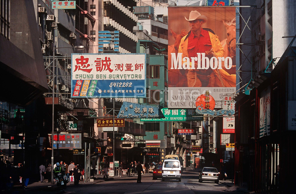 While still a British colony, 1990s street advertising including one for the cigarette Marlboro Man, on 21st April 1995, in Kowloon, Hong Kong, China.