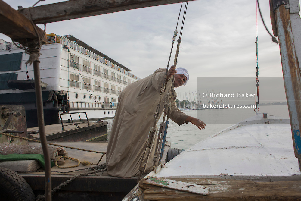 A crewman of a felucca readies his sailing boat before sailing on the River Nile at Luxor, Nile Valley, Egypt. Feluccas are ancient Egyptian sail boats which were used in ancient times as a primary mode of transport and are the only type of boat that is still used extensively in the country.
