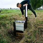 """Nederland Kronenberg 30 september 2008 20080930 Foto: David Rozing ..Serie vernattingscampagne """" Nieuw Limburgs Peil """" de Peel ..Waterschapper Frans van Munnickhof inspecteert watergang / stuwtje. Vernattingscampagne """" Nieuw Limburgs Peil """" in omgeving de Peel, uitgevoerd door o.a. de  plaatselijke boeren in samenwerking met het waterschap Peel en Maasvallei. Het doel is een hoger peil van het grondwater dmv het vasthouden van hemelwater. Dit  wordt verwezenlijkt door de aanleg van stuwen in de watergangen bij bv akkers. Door de stuwen in de sloten/ watergangen dicht te zetten wordt het grondwaterpeil hoger in het gebied. Voordelen hiervan zijn: verdroging van de natuur wordt tegen gegaan, voor de boeren kan het drie beregeningen per jaar besparen. Boerenpeil: 400 van de inmiddels 1250 stuwen worden beheerd door de boeren. Natuurgebieden als De Grote Peel en Maria peel hebben veel te lijden gehad onder eerder .waterbeheer:  Het waterschap heeft in het verleden veel akkerslootjes, beken en kanaaltjes aangelegd om ervoor te zorgen dat het water rond dit natuurgebied snel kon wegvloeien, zodat de oogsten.niet zouden verrotten en de akkers goed bewerkbaar waren, maar waardoor nu het waterpeil erg snel zakt..Medewerkers van het waterschap bezoeken de boeren thuis en voeren keukentafelgesprekken met hen om ze te betrekken bij het project. .De Peel is een grotendeels verdwenen hoogveengebied op de grens van de Nederlandse provincies Noord-Brabant en Limburg. ..Foto David Rozing"""