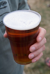 Closeup of a man's hand holding a pint of beer,