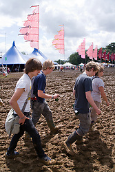 Young, festival goers forced to wear Wellington boots when heavy rain brings muddy ground at WOMAD (World of Music; Arts and Dance) Festival; Charlton Park; Malmesbury; 2007,