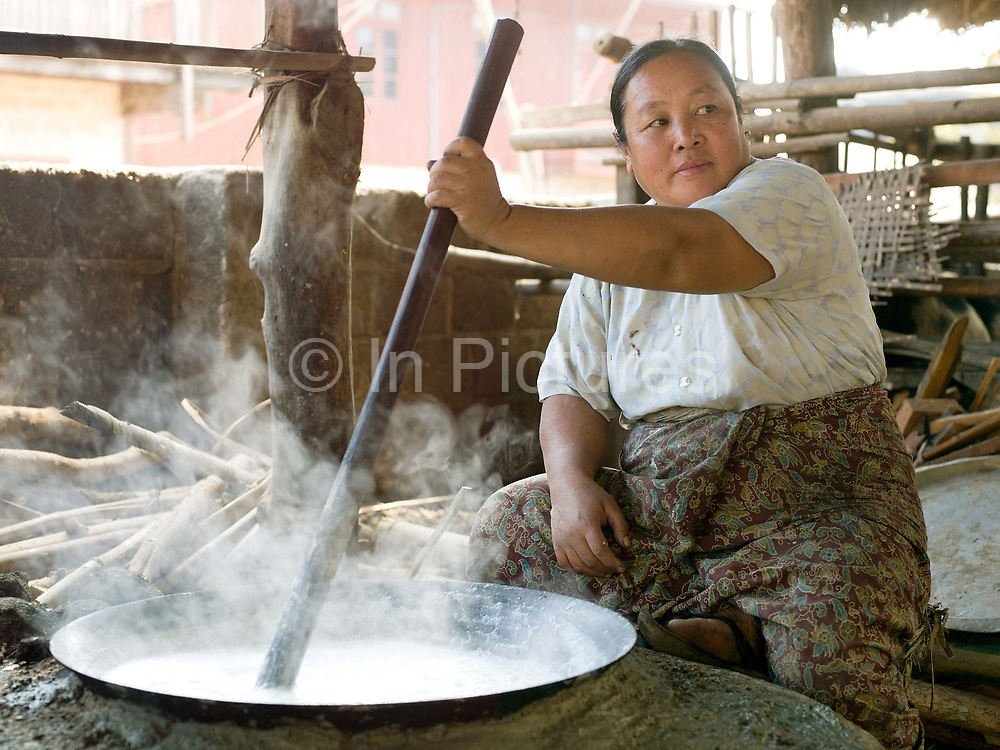 An Intha woman stirs a pan of tofu she is making over a fire, Kaung Daing village Shan State, Myanmar (Burma).  Located on the northwestern shore of Inle Lake, the Intha village of Kaung Daing is known for its tofu, prepared using split yellow peas instead of soybeans.