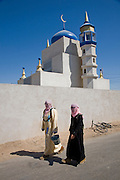 Women in burqas walk past an abandoned bicycle outside a mosque in the fabricated Iraqi village of Medina Wasl at Camp Irwin, California in the Mojave Desert.  The village is used for training soldiers deploying to Iraq.