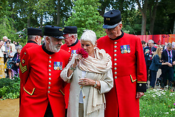 © Licensed to London News Pictures. 20/09/2021. London, UK. Dame Judi Dench (C) smells a flower with Chelsea pensioners in The RHS Queen's Green Canopy Garden during press day for the RHS Chelsea Flower Show. The RHS Chelsea Flower Show is a garden show held by the Royal Horticultural Society in the grounds of the Royal Hospital Chelsea. It has been held since 1912 and this year the show will be spread over six days instead of five (from 21 to 26 September), with reduced numbers of visitors on each of the days. The annual flower show was postponed in May due to the coronavirus lockdown. Photo credit: London News Pictures