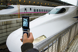 Photographing a shinkansen bullet train with a camera phone at Tokyo railway station