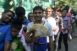 November 13, 2016 - Kolkata, West Bengal, India - Indian shows Rs. 500 and Rs. 1000 bank note and long time waiting to exchange it in front of State Bank of India...To facilitate smooth exchange and deposit the old Rs. 500 and Rs. 1000 bank note bank across India remain open for public on Sunday , as announced by Union Government after demonetized Rs.500 and Rs.1000 bank notes to tackle the menace of black money. Indian line up outside the banks to deposit and exchange demonetized bank note from late night. (Credit Image: © Saikat Paul/Pacific Press via ZUMA Wire)
