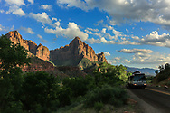 Zion's massive sandstone cliffs of red against blue sky in late afternoon sun. Photo taken in Springdale  at park's main entrance May 10, 2016.