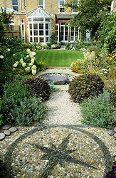 View from the back of the garden towards the house. Pebble mosaic in the foreground with circular water feature and lawn beyond