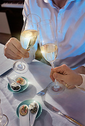 Couple toasting champagne glasses at dinner table