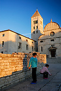 Two children (9 years old, 5 years old), playing near wall, Church of St. Mary (Crkva Sveti Marije) in background, in late afternoon sunlight. Zadar, Croatia