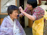 Bhutanese woman having a street haircut in the small town of Trashigang, Eastern Bhutan.
