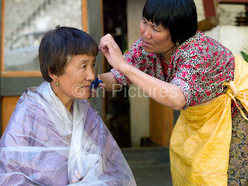 Bhutanese woman having a street haircut in the small town of Trashigang, Eastern Bhutan.