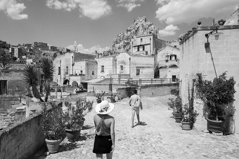 Visitors walk through the streets of Sassi di Matera on July 24, 2020. Sassi di Matera are two districts (Sasso Caveoso and Sasso Barisano) of the Italian city of Matera, Basilicata, well-known for their ancient cave dwellings inhabited since the Paleolithic period.