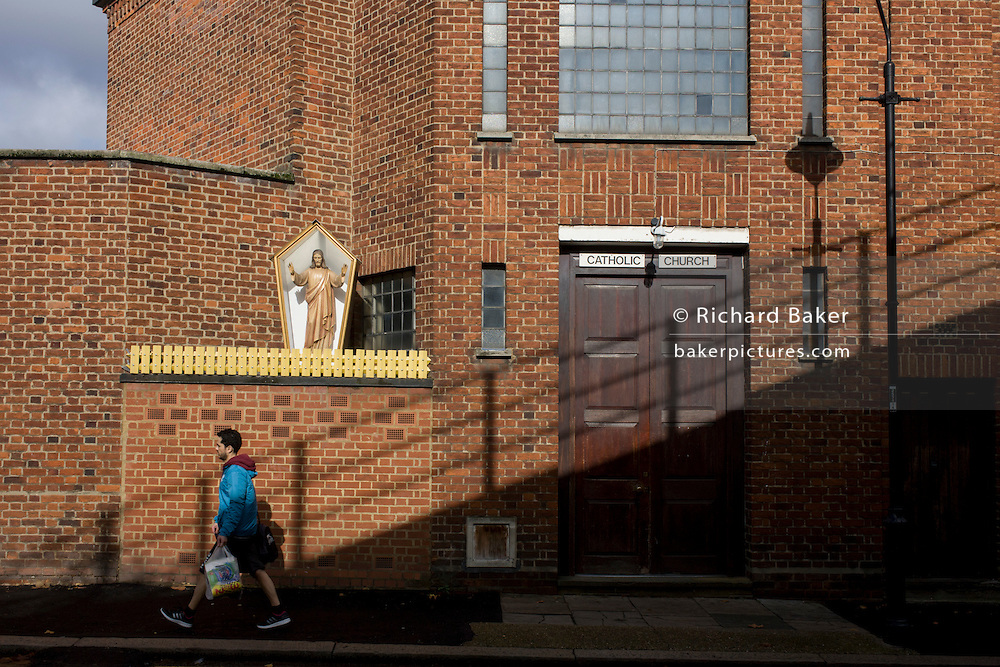 Woman looks up at an effigy of Jesus Christ encased in a shrine box outside a Catholic church in Camberwell, south London.