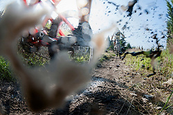 Mountain bikers riding through muddy puddle, Ore Mountains, Saxony, Germany
