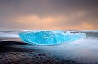 JOKULSARLON, ICELAND - CIRCA MARCH 2015: Iceberg on the sand black beach near to the Jökulsárlón lagoon in Iceland on the edge of Vatnajökull National Park