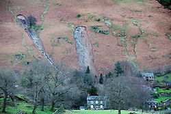 © Licensed to London News Pictures. 10/12/2015. Patterdale UK. Picture shows two huge landslides behind a house in Patterdale near the village of Glenridding that has flooded for a second time this week after the beck broke it's banks. Photo credit: Andrew McCaren/LNP