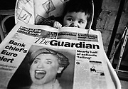 """First ladies."" A six month-old infant girl has a shocked look on her face as she plays with a copy of the broadsheet Guardian newspaper whose front page headline photograph is of Hilary Clinton, then First Lady of the United States. Clinton is also looking aghast at something she is experiencing. Coincidentally, the President's wife and the first-born of this family are both first ladies. The child has sunk down into her high-chair, reacting to something her mother has said. This is from a documentary series of pictures about the first year of the photographer's first child Ella. Accompanied by personal reflections and references from various nursery rhymes, this work describes his wife Lynda's journey from expectant to actual motherhood and for Ella - from new-born to one year-old."