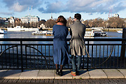 Two people look out over the River Thames towards Temple, from the riverside walkway on the South Bank. London, UK.