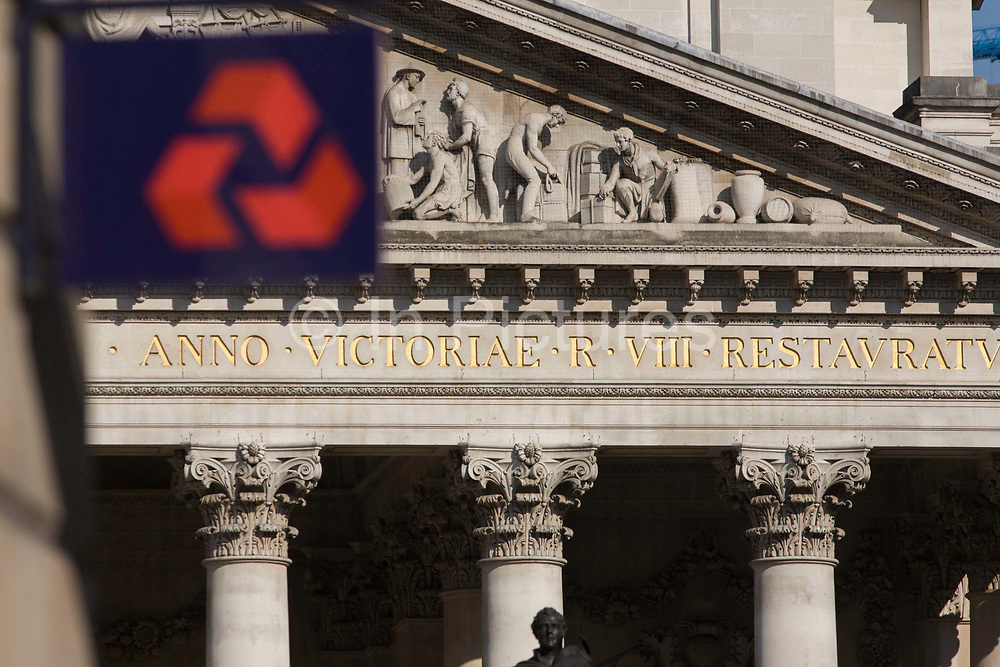 Natwest Bank plc sign and architecture of Cornhill Exchange, City of London. Focus is on the neo-Roman architecture of Cornhill's exchange building behind. At the top of Doric and Ionic columns with their ornate stonework, powerfully strong lintels cross, bearing the load of fine artistry and carvings which feature the design by Sir William Tite in 1842-1844 and opened in 1844 by Queen Victoria whose name is written in Latin (Victoriae R). NatWest is the largest retail and commercial bank in the United Kingdom. Since 2000, it has been part of The Royal Bank of Scotland Group, ranked among the top 10 largest banks in the world by assets. Today it has more than 7.5 million personal customers and 850,000 small business accounts. In Ireland it operates through its Ulster Bank subsidiary.