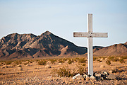 A white cross in the desert designates the location of a traffic death in California.
