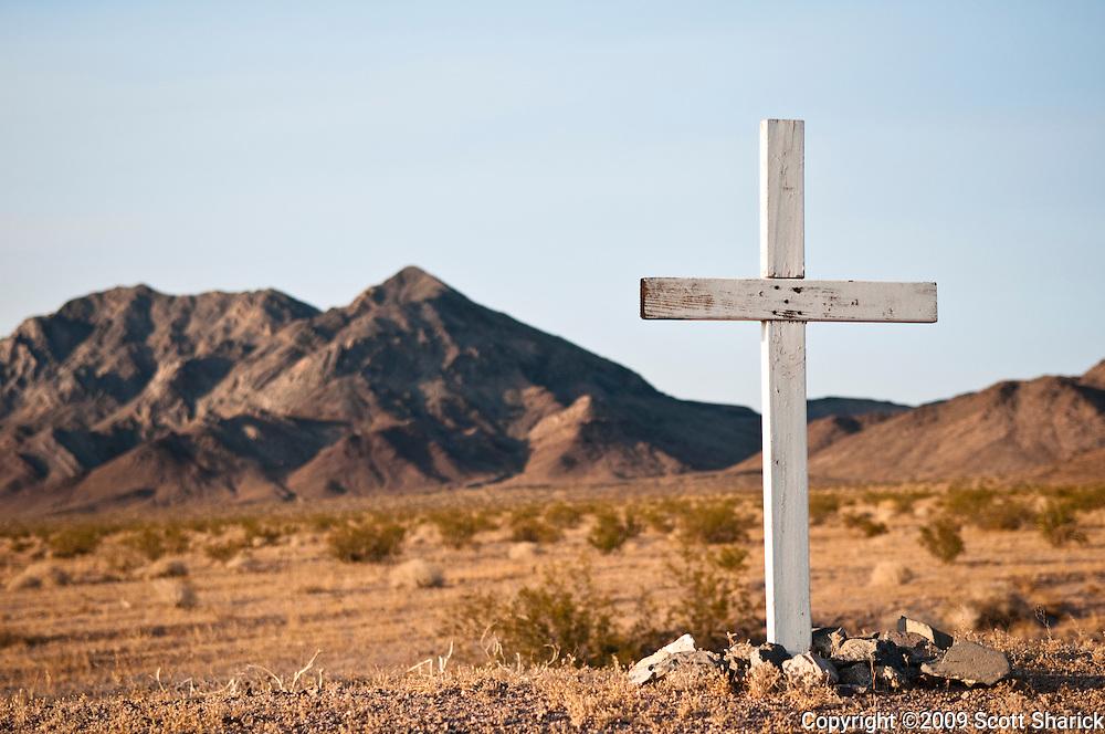 A white cross in the desert designates the location of a traffic death in California.