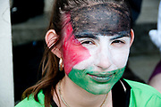 Demonstration against Israeli bombing of Gaza, 26.07.2014. Taking a selphie. Young woman with face painted in the colours of the Palestinian flag. London, England, UK.