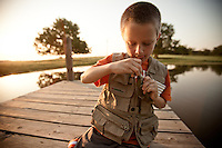 YOUNG BOY ANGLER WITH A NEWLY CAUGHT BLUEGILL SUNFISH