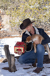 puppy and a cowboy opening a Christmas package outdoors