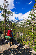 Backpacker on trail in the John Muir Wilderness, Sierra Nevada Mountains, California USA