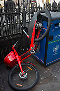 A damaged and abandoned Uber rental bike is propped up next to a City of London recycling receptacle at Bank Underground Station in the capital's financial district, on 6th March 2020, in London, England.