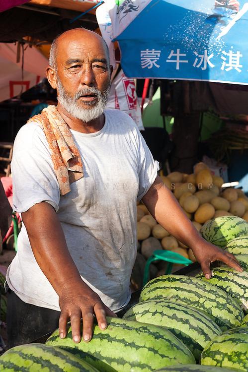 Uyghur man selling melons at the bazar, Turpan, Xinjiang, China