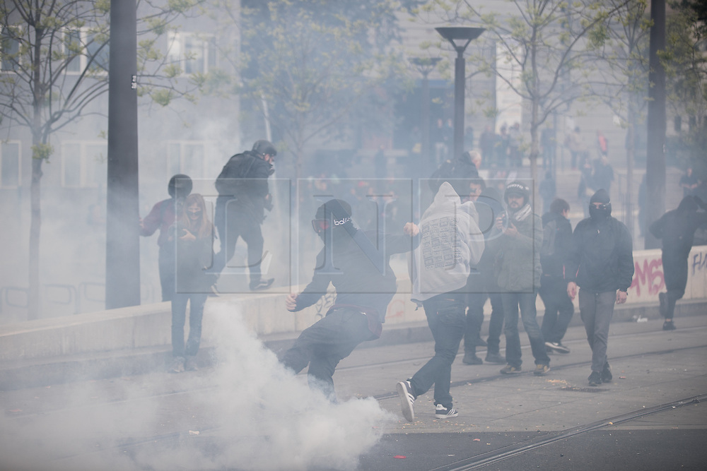 © Licensed to London News Pictures. 16/04/2017. Paris, France. Protesters and riot police clash as protesters throw bottles , flares and rocks and police launch tear gas . Antifascist protesters opposed to a meeting by French far-right party , Front National , hold a demonstration in the North East of Paris . Photo credit: Joel Goodman/LNP