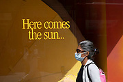 Here comes the sun... yellow slogan in a shop window on Oxford Street on 10th August 2021 in London, United Kingdom.
