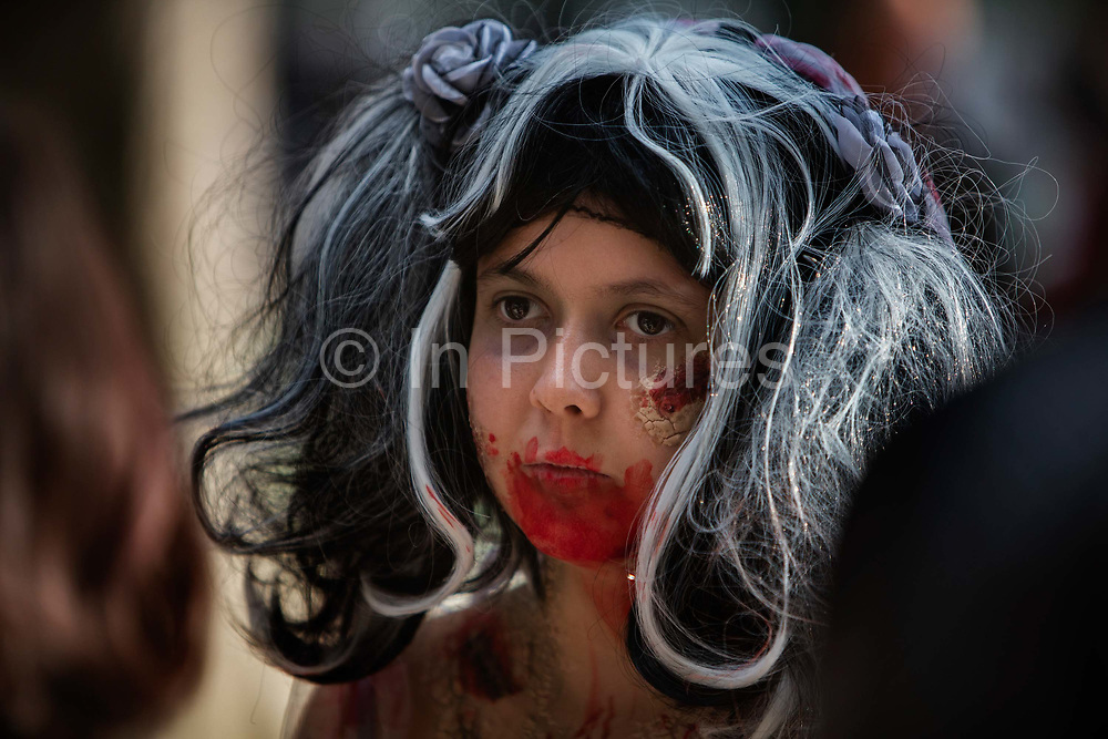 A portrait of a girl with zombie make-up on her face, one of 2000 Goules who took part in the Zombie Walk, 8th October 2016, Paris, France. The walk went from Place de la Republique and finished at Place des Vosges. The event, an apocalyptic parade through Paris's historic downtown. Zombie walks as annual traditions are now relatively common in large cities, especially in North America.