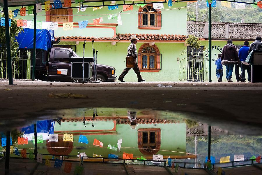A man is reflected in a pool of water during the patron saint festival at San Pedro Chenalho, a Tzotzil Mayan village outside San Cristobal de las Casas, Chiapas, Mexico on June 27, 2008.