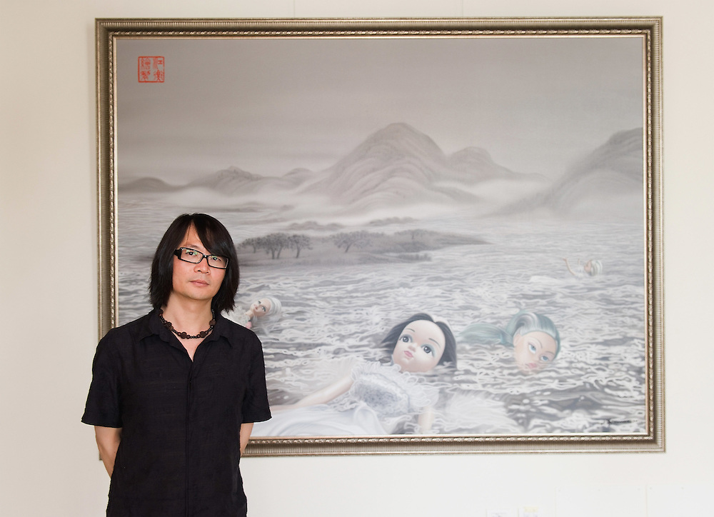 """VENICE, ITALY - JUNE 02:  Artist Jeang Heng  poses  in front of """"Gift from Ruth Handler"""" a painting  part of the Exhibition Future Pass on June 2, 2011 in Venice, Italy. The Venice Art Biennale will run from June 4 to November 27, 2011."""