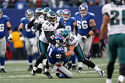 11 Jan 2009: Philadelphia Eagles linebacker Stewart Bradley #55 and cornerback Joselio Hanson #21 tackle New York Giants wide receiver Amani Toomer #81 during the game against the New York Giants on January 11th, 2009.  The  Eagles won 23-11 at Giants Stadium in East Rutherford, New Jersey. (Photo by Brian Garfinkel)