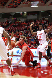 29 November 2014:  Bobby Hain works his way into the lane against John Jones but stumbles as the four feet become entangled during an NCAA men's basketball game between the Youngstown State Penguins and the Illinois State Redbirds  in Redbird Arena, Normal IL.