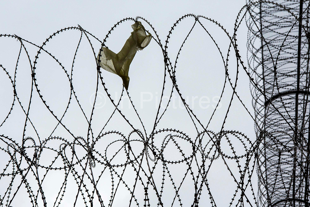 Razor wire security fencing inside HMP/YOI Portland, a resettlement prison with a capacity for 530 prisoners. Dorset, United Kingdom.