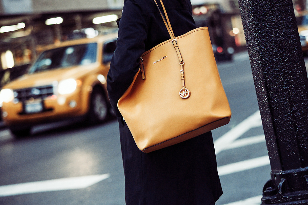 Woman with orange bag on NYC street with cab. NYC 2012