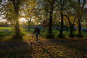 A cyclist pedals through an Autumnal park. Surrounded by autumn leaves, brown and yellow in afternoon sunlight, the man cycles through sunlight during a burst of afternoon sunshine in Ruskin Park in the London borough of Lambeth. In the background are Edwardian period homes on Finsen Road, SE24.